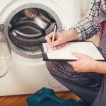 Repairman is repairing a washing machine on the white background