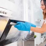 Woman Opening Door Of Oven Full Of Smoke