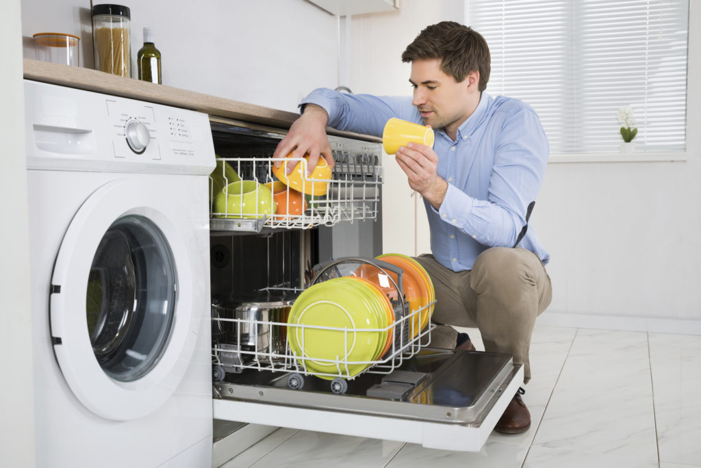 Young Happy Man Arranging Dishes In Dishwasher In Modern Kitchen