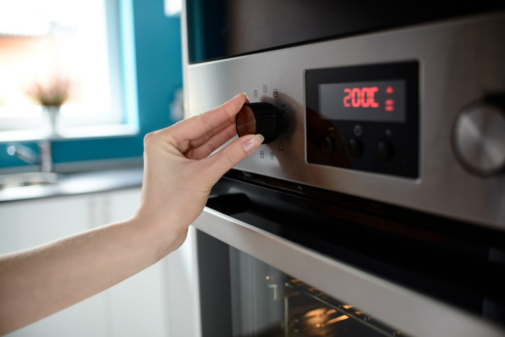Close up of woman's hand setting temperature control on oven. The display shows the set temperature to 200 degrees Celsius