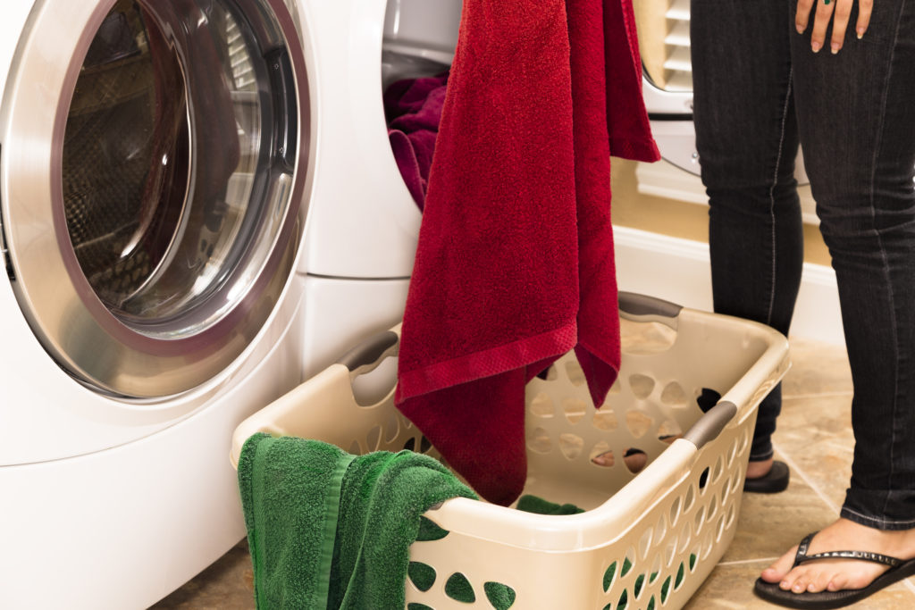 Domestic Life: Woman removing towels from clothes dryer to Laundry basket