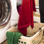 Domestic Life:  Woman removing towels from clothes dryer.  Laundry basket