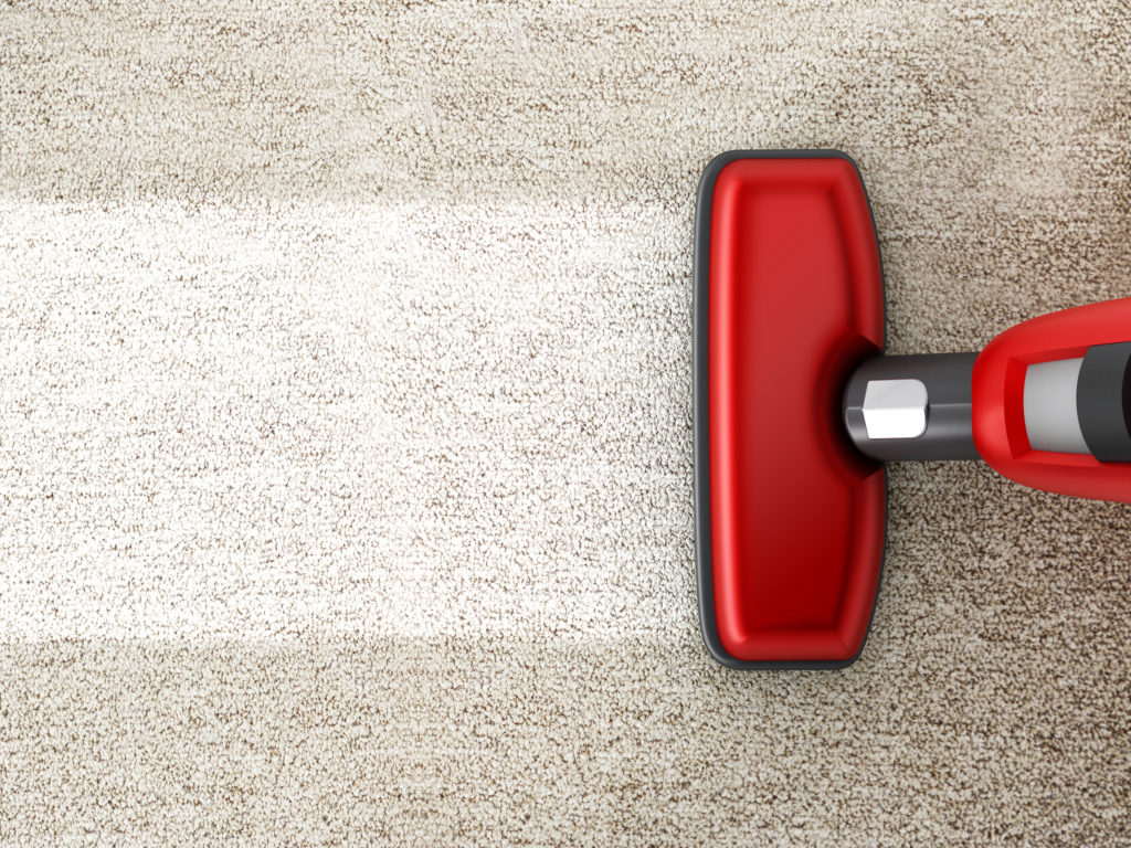 Red vacuum cleaner cleaning a carpet.