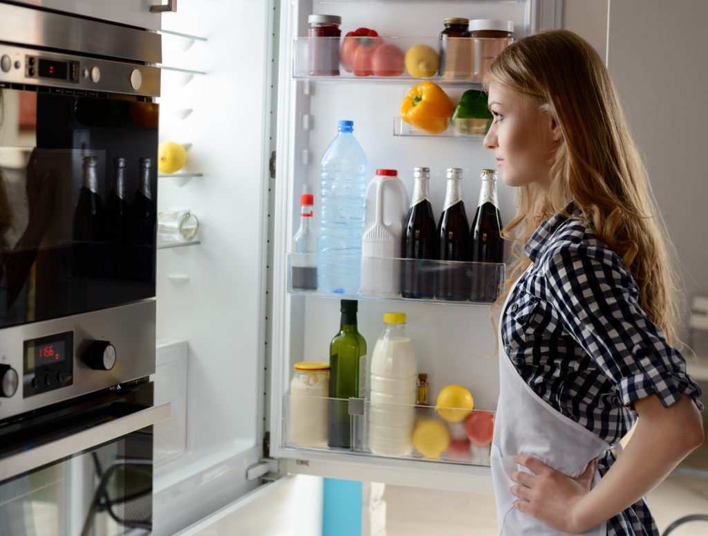 Woman with open refrigerator. She is wondering what to pull. You can see a bottle of beer, chocolate butter, pepper, lemon, milk, eggs