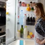 Woman with open fridge