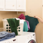 Domestic Life:  Young adult hanging shirts right out of dryer