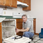 Plumber Working in Kitchen